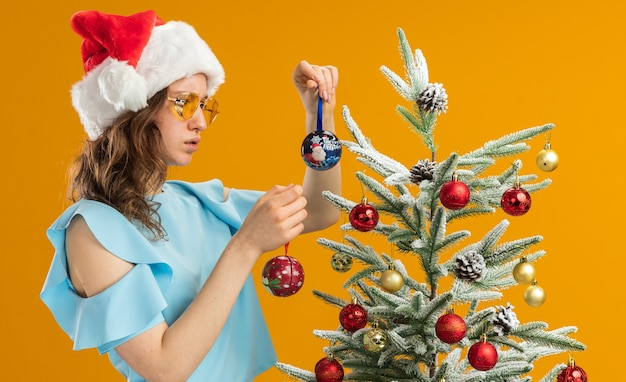 Young woman in blue top and santa hat wearing yellow glasses holding christmas balls looking confused having doubts standing next to a christmas tree over orange background Free Photo