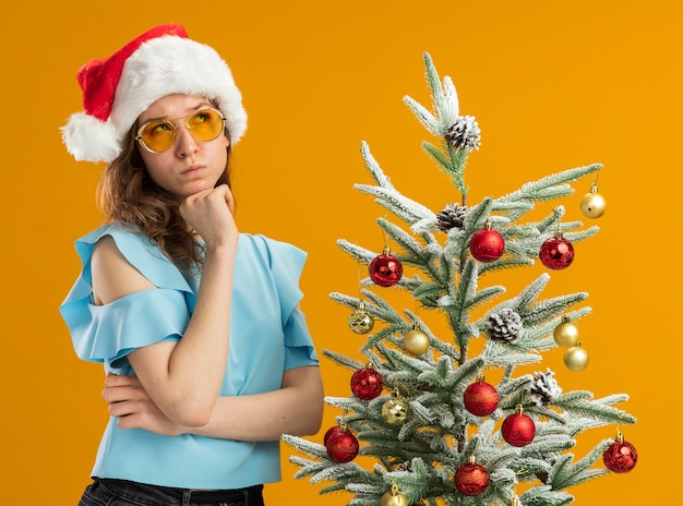 Young woman in blue top and santa hat wearing yellow glasses looking up puzzled standing next to a christmas tree over orange background