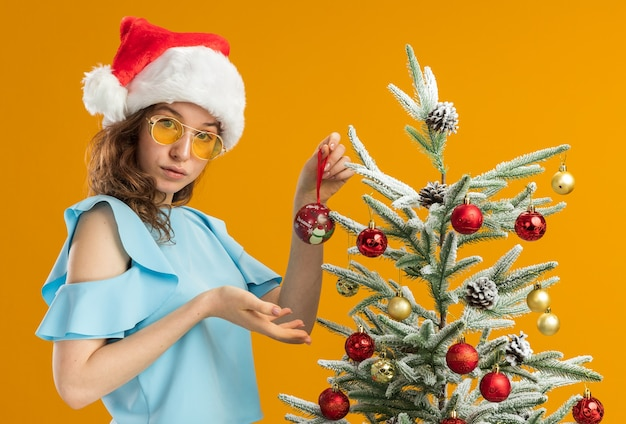 Giovane donna in top blu e cappello da babbo natale che indossa occhiali gialli in piedi accanto a un albero di natale che tiene la palla di natale che lo presenta con un braccio che sembra sicuro sul muro arancione