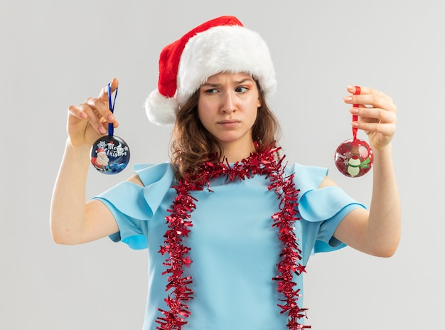Young woman in blue top and santa hat with tinsel around her neck holding christmas balls looking confused trying to make choice