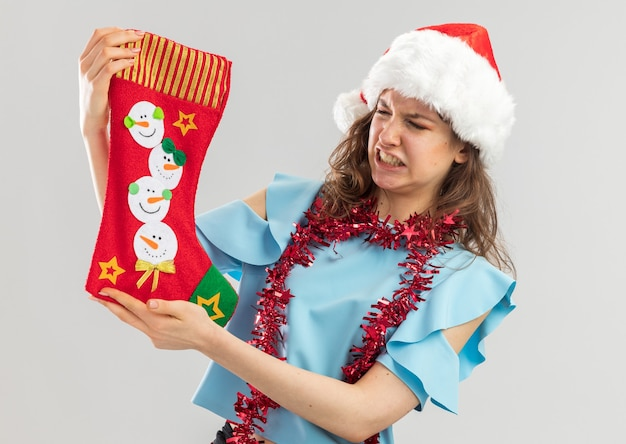 Young woman in blue top and santa hat with tinsel around her neck holding christmas stocking looking at it with disgusted expression