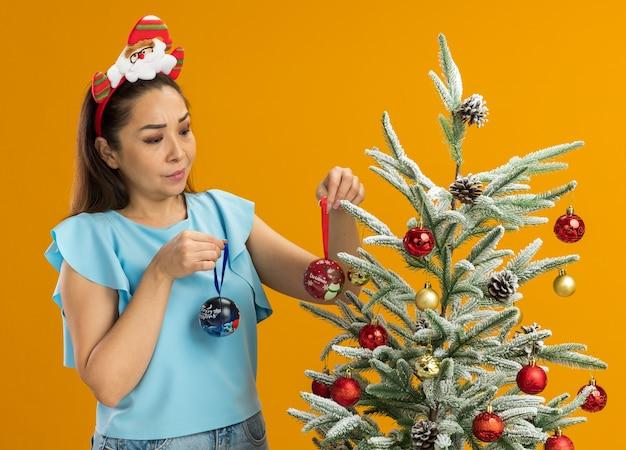 Giovane donna nella parte superiore blu che porta il bordo divertente di natale sulla testa che tiene le palle di natale che appendono sull'albero di natale che sembra confuso sopra la condizione arancione sopra fondo