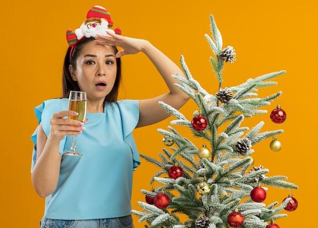 Giovane donna nella parte superiore blu indossando divertenti bordo di natale sulla testa tenendo un bicchiere di champagne guardando lontano di essere sorpreso in piedi accanto a un albero di natale su sfondo arancione