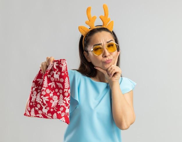 Giovane donna nella parte superiore blu che porta l'orlo divertente con le corna dei cervi e gli occhiali gialli che tengono la borsa rossa di natale che osserva con la mano sul pensiero del mento