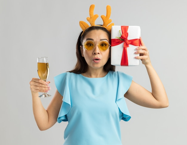 Young woman in blue top wearing funny rim with deer horns and yellow glasses holding glass of champagne and christmas present looking surprised and worried