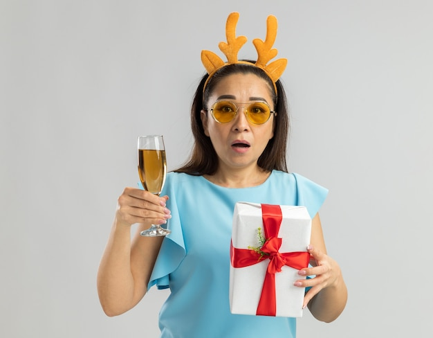 Young woman in blue top wearing funny rim with deer horns and yellow glasses holding glass of champagne and christmas present looking worried and confused