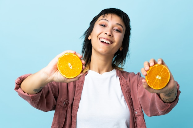 Young woman over blue wall holding an orange