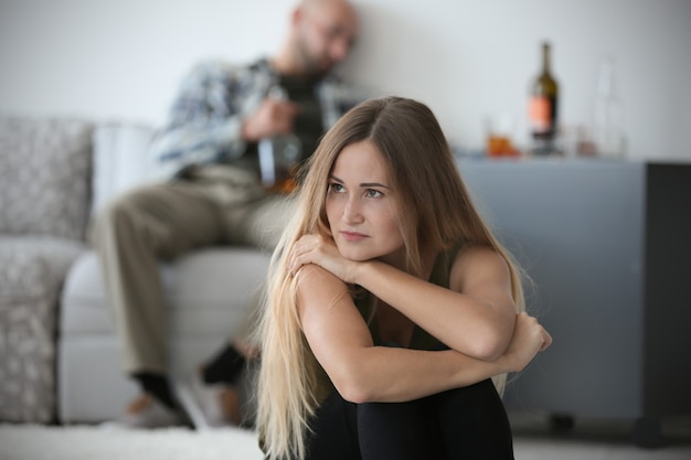 Young woman and blurred man with bottle of alcohol at home