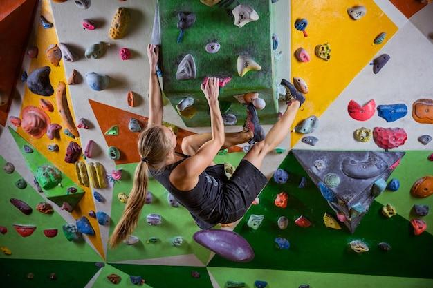 Молодая женщина боулдеринг на нависающей стене в крытом тренажерном зале для скалолазания