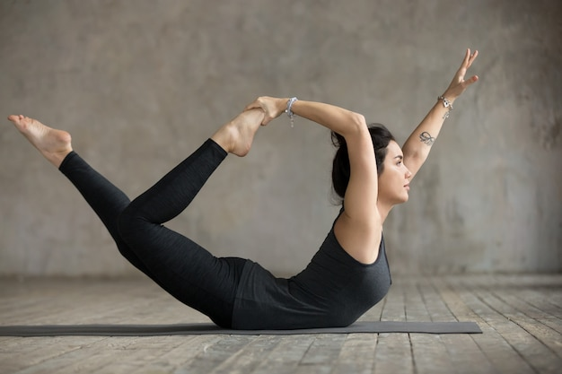 Young woman in bow pose