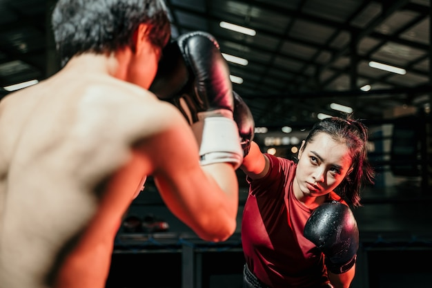 Young woman boxer doing exercise punching competing with man opponent at boxing camp