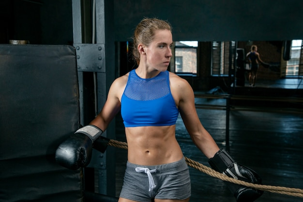 若い女性のボクサーはボクシングのリングのロープの近くに立っています