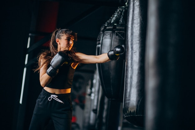 Young woman boxer training at the gym