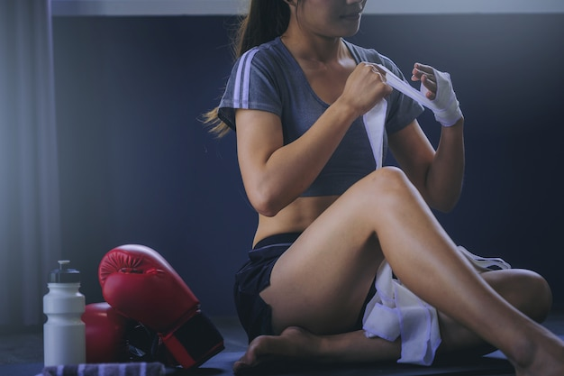 Young woman boxer wearing strap on wrist ready for boxing exercise.