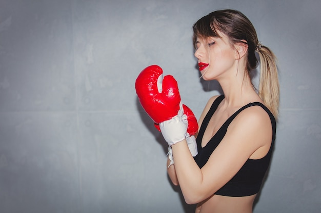 Young woman in boxing gloves on gray background. 90s flashlight style