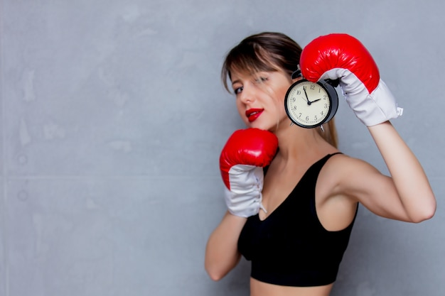 Young woman in boxing gloves with alarm clock