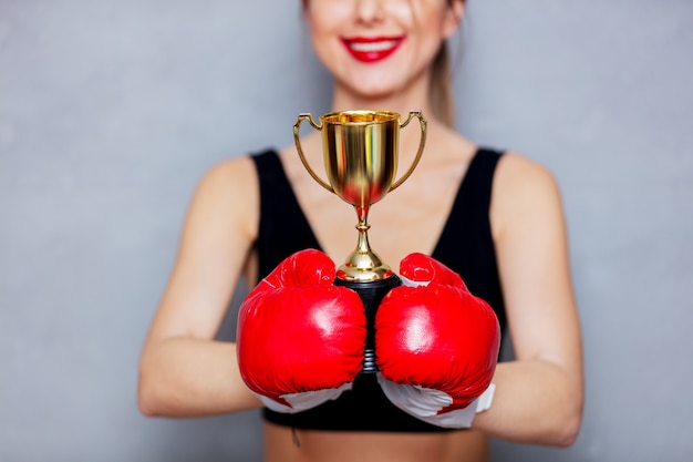 Young woman in boxing gloves with golden cup on gray background. 90s flashlight style