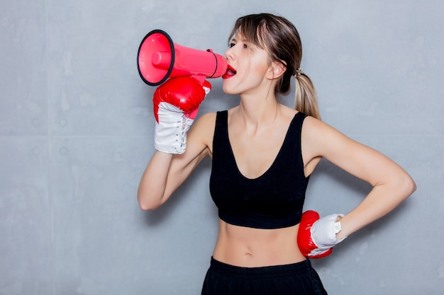 Young woman in boxing gloves with loud speaker on gray background. 90s flashlight style