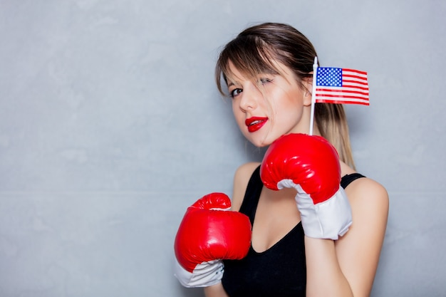 Young woman in boxing gloves with usa flag on gray background. 90s flashlight style