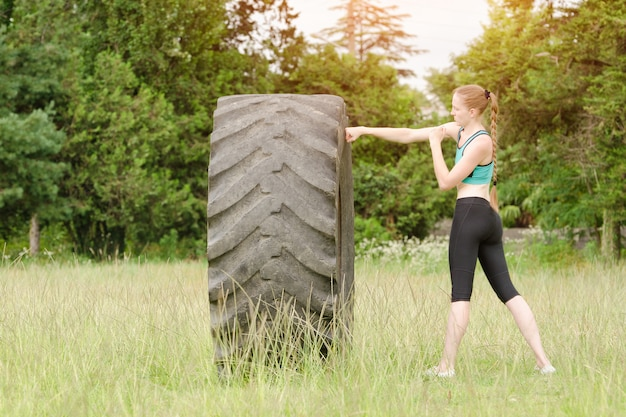 Young woman boxing with the tire. workout