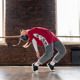 Young woman breakdancing in the dance studio