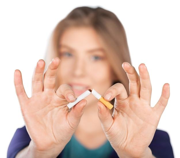 背景にタバコを壊す若い女性