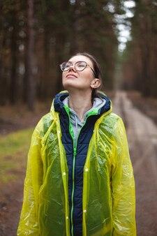 젊은 여성은 비가 내린 후 숲에서 신선한 공기를 마시고, 휴식을 취하고, 노란색 비옷을 입고, 눈을 감고 숨을 쉰다