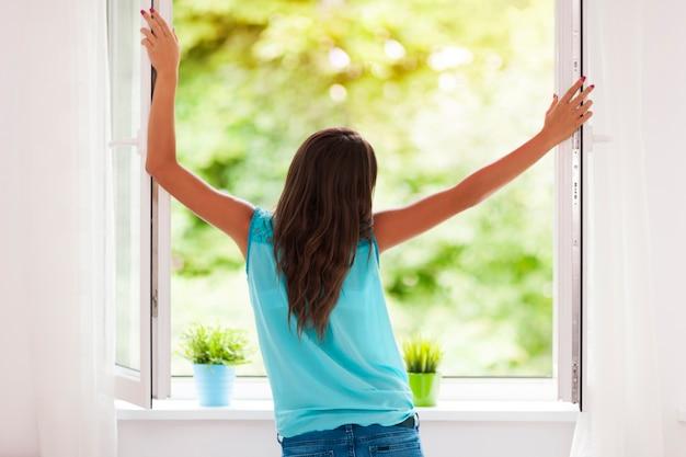 Молодая женщина дышит свежим воздухом летом