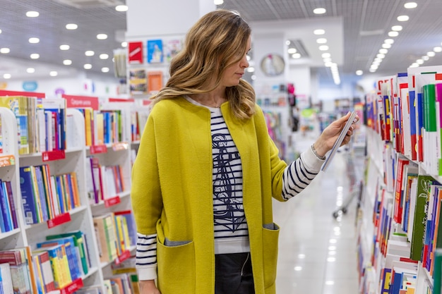 Young woman in a bright coat chooses a children's book in a store. education and leisure.