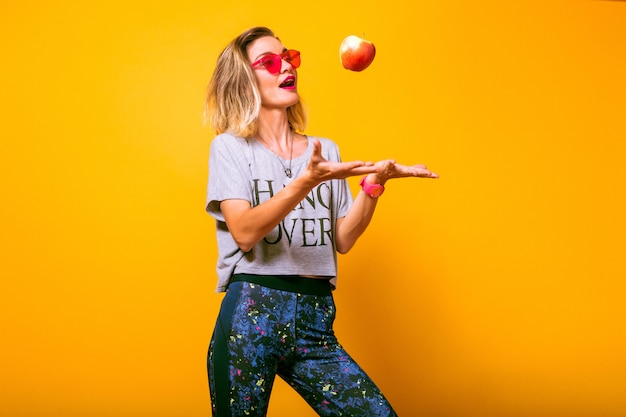 Young woman in bright sportive outfit playing with apple