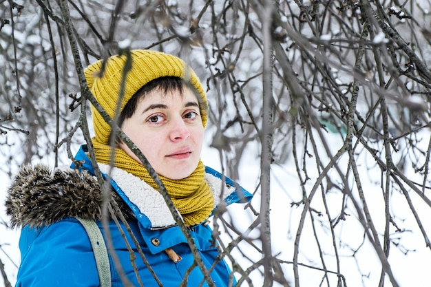 Young woman in bright winter hat and jacket among branches of trees in winter park.