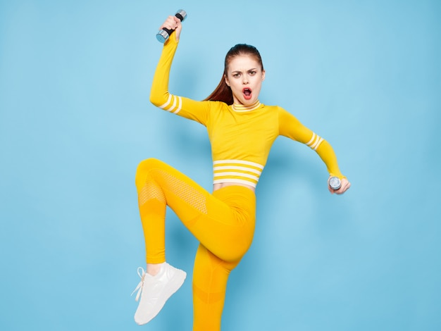 Young woman in a bright yellow sports suit with dumbbells does sports on a blue surface