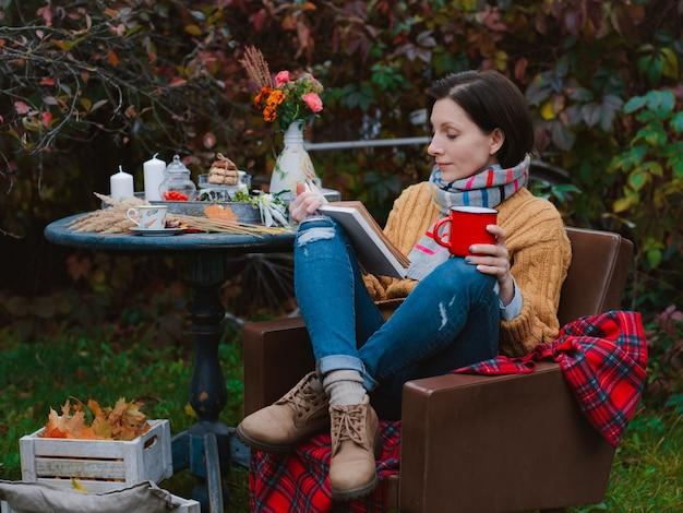 Молодая женщина в коричневом пальто сидит на стуле за столом и читает книгу с накинутой на голову клеткой на открытом воздухе на фоне покрасневшей осенней листвы
