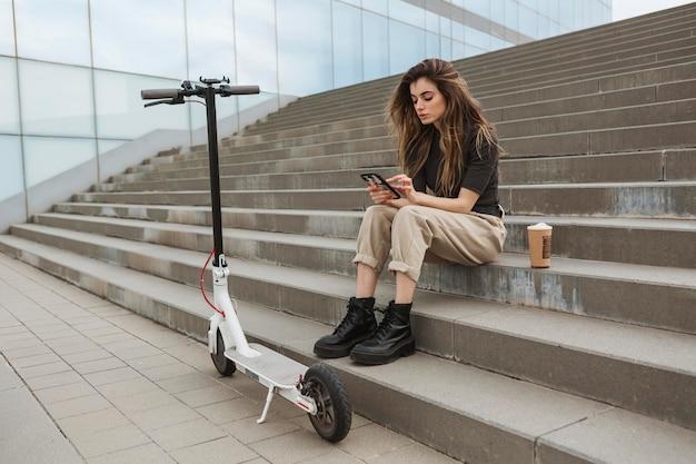 Молодая женщина просматривает свой мобильный телефон