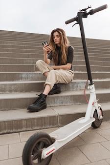 Giovane donna che passa in rassegna il suo telefono cellulare
