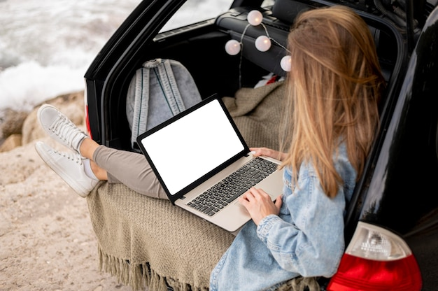 Young woman browsing laptop on road trip