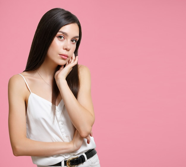 Young woman brunette girl on a pink background