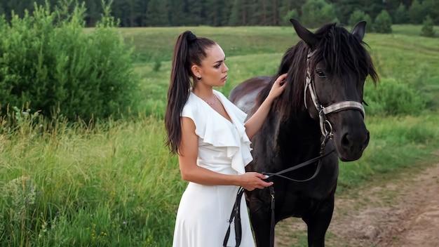Молодая женщина брюнетка с волосами в хвосте домашних животных черная лошадь