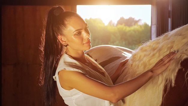 Young woman brunette with long hair in ponytail pets horse