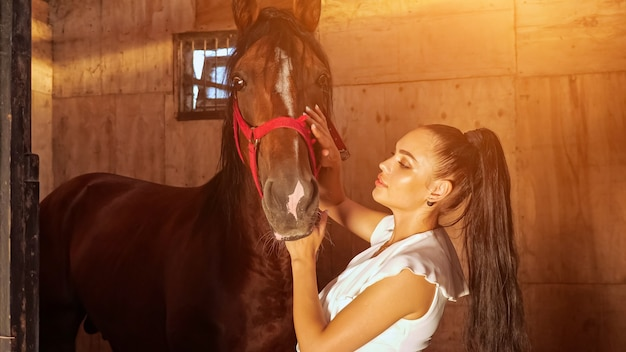 Young woman brunette with ponytail kisses horse with smile