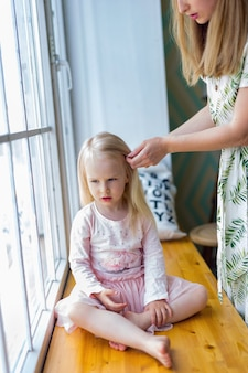 Young woman brushing pretty girl's hair while sitting in front of window. woman combing her blonde daughter's hair