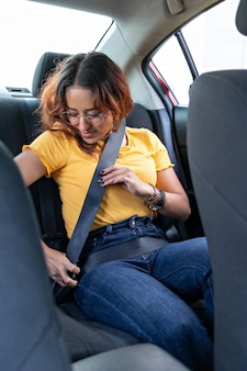 A young woman buckling her seat belt in the back seat of a car