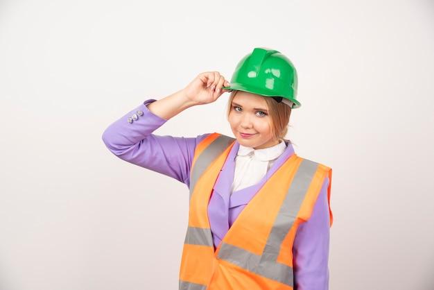 白い壁にヘルメットをかぶった若い女性ビルダー。