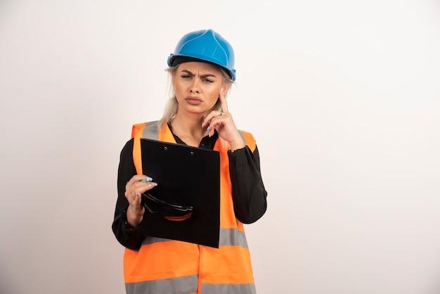 クリップボードで目をそらしている若い女性ビルダー。高品質の写真
