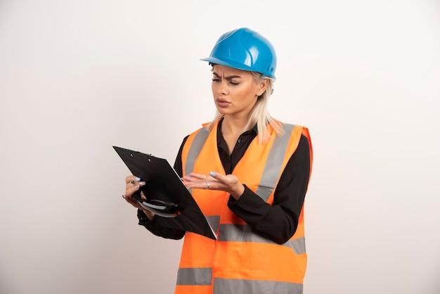 クリップボードを探している若い女性ビルダー。高品質の写真