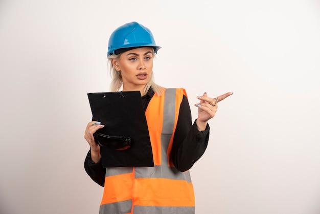 どこかを指しているクリップボードを持つ若い女性ビルダー。高品質の写真