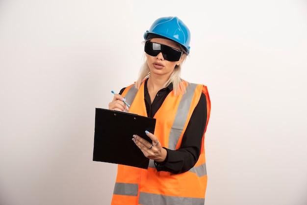 ゴーグルとクリップボードを持つ若い女性ビルダー。高品質の写真
