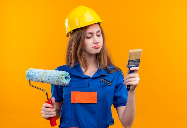 Young woman builder worker in construction uniform and safety helmet holding brush and paint roller looking at brush with skeptic expression standing over orange wall