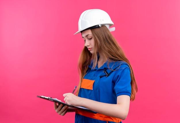 Operaio del costruttore della giovane donna in uniforme da costruzione e casco di sicurezza che tiene appunti esaminandolo scrivendo in piedi sopra il muro rosa