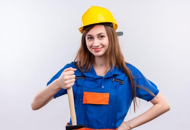Operaio del costruttore della giovane donna in uniforme da costruzione e casco di sicurezza che tiene martello sorridente in piedi sopra il muro bianco